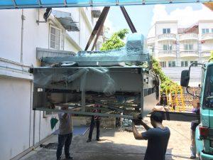 เครื่องตัดผ้าอัตโนมัติถูกลำเลียงเข้าสู่อาคาร