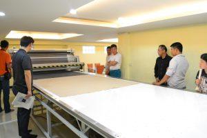ชาวต่างชาติดูระบบเครื่องตัดผ้าอัตโนมัติ